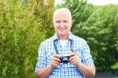 Homme supérieur heureux prenant des photos en parc Photo stock