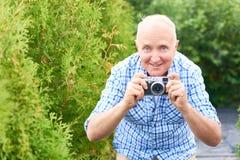 Homme supérieur heureux prenant des photos en parc Image libre de droits