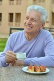 Homme supérieur heureux prenant le petit déjeuner Photo libre de droits