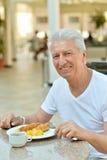Homme supérieur heureux prenant le petit déjeuner Photographie stock libre de droits