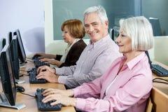 Homme supérieur heureux s'asseyant au bureau dans la classe d'ordinateur Image libre de droits