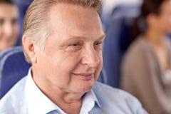 Homme supérieur heureux s'asseyant dans l'autobus ou l'avion de voyage Images stock