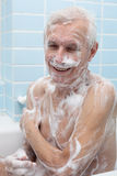 Homme supérieur heureux se baignant Photographie stock libre de droits