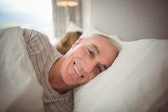 Homme supérieur heureux se trouvant sur le lit photographie stock