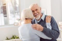 Homme supérieur heureux souriant tout en dansant avec l'épouse Photographie stock