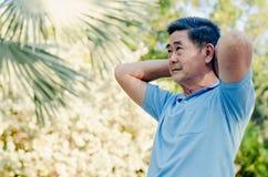 Homme supérieur heureux sur une promenade avec le brassard faisant l'étirage à l'arrière-plan vert de nature Nature d'automne photo libre de droits