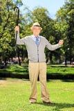 Homme supérieur heureux tenant et faisant des gestes le bonheur en parc Image stock