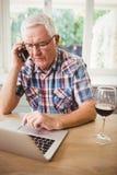 Homme supérieur inquiété prenant le téléphone tout en à l'aide de l'ordinateur portable Image libre de droits