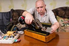 Homme supérieur inspectant la machine à coudre de vintage Image stock