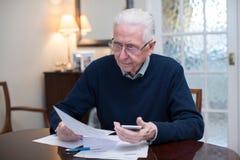 Homme supérieur intéressé passant en revue des finances domestiques photo stock