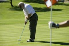 Homme supérieur jouant au golf Image stock