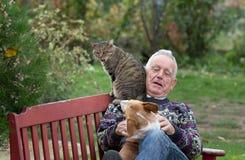 Homme supérieur jouant avec des animaux familiers Photos libres de droits