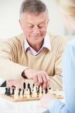 Homme supérieur jouant des échecs avec la petite-fille adolescente Photos libres de droits