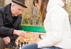 Homme supérieur jouant des échecs avec sa petite-fille Photographie stock