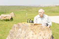 Homme supérieur jouant des échecs sur une roche Photo libre de droits