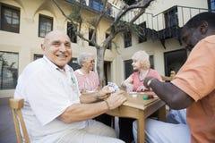 Homme supérieur jouant des cartes avec des amis Photos stock
