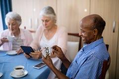 Homme supérieur jouant des cartes avec des amis tout en ayant le café Images libres de droits