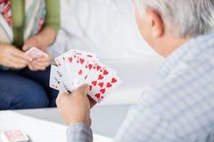 Homme supérieur jouant des cartes avec l'ami féminin Photographie stock libre de droits