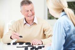 Homme supérieur jouant des dominos avec la petite-fille adolescente Image libre de droits