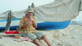 Homme supérieur jouant la cannelure en bambou sur la plage à côté du bateau de pêche clips vidéos