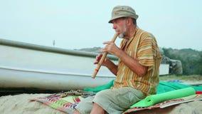 Homme supérieur jouant la cannelure en bambou sur la plage à côté du bateau de pêche banque de vidéos