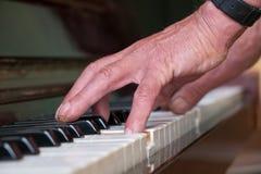 Homme supérieur jouant le piano Photographie stock