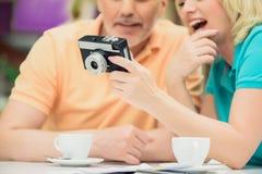 Homme supérieur joyeux et femme regardant des tirs Photo stock