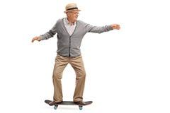 Homme supérieur joyeux montant une planche à roulettes photo libre de droits