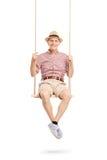 Homme supérieur joyeux s'asseyant sur une oscillation et une pose Images stock