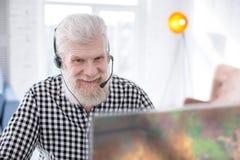 Homme supérieur joyeux souriant tout en jouant le jeu en ligne Images libres de droits