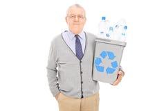 Homme supérieur jugeant une poubelle de réutilisation pleine des bouteilles en plastique Image libre de droits