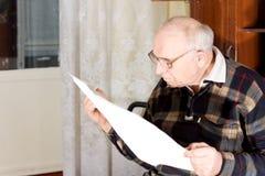 Homme supérieur lisant un journal Photographie stock libre de droits