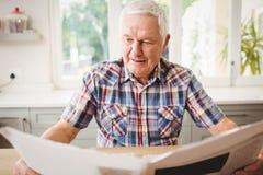 Homme supérieur lisant un journal Photos stock