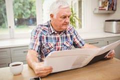 Homme supérieur lisant un journal Photographie stock
