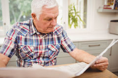 Homme supérieur lisant un journal Image stock