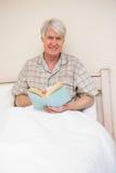 Homme supérieur lisant un livre dans le lit Photographie stock