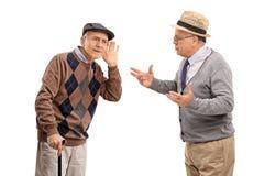 Homme supérieur luttant pour entendre un ami Photographie stock