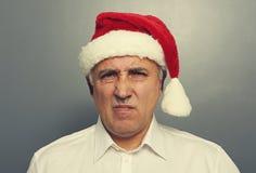 Homme supérieur mécontent dans le chapeau de Santa Image stock