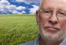Homme supérieur mélancolique avec le champ d'herbe derrière Photos stock
