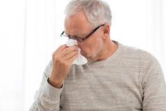 Homme supérieur malade avec le chiffon de papier soufflant son nez photo libre de droits