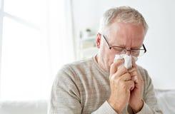 Homme supérieur malade avec le chiffon de papier soufflant son nez image libre de droits