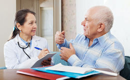 Homme supérieur malade portant plainte au docteur au sujet de la malaise Image stock
