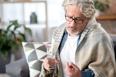 Homme supérieur malade réfléchi prenant le médicament Photo libre de droits