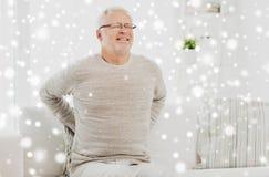 Homme supérieur malheureux souffrant du mal de dos à la maison Photos stock