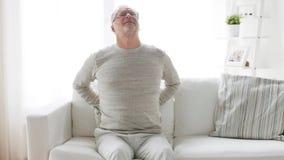 Homme supérieur malheureux souffrant du mal de dos à la maison 28 banque de vidéos