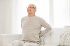 Homme supérieur malheureux souffrant du mal de dos à la maison Photos libres de droits