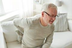 Homme supérieur malheureux souffrant du mal de dos à la maison Images stock