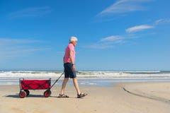 Homme supérieur marchant avec le chariot à la plage Photos stock