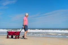 Homme supérieur marchant avec le chariot à la plage Photographie stock libre de droits