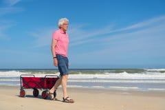 Homme supérieur marchant avec le chariot rouge à la plage Photo stock